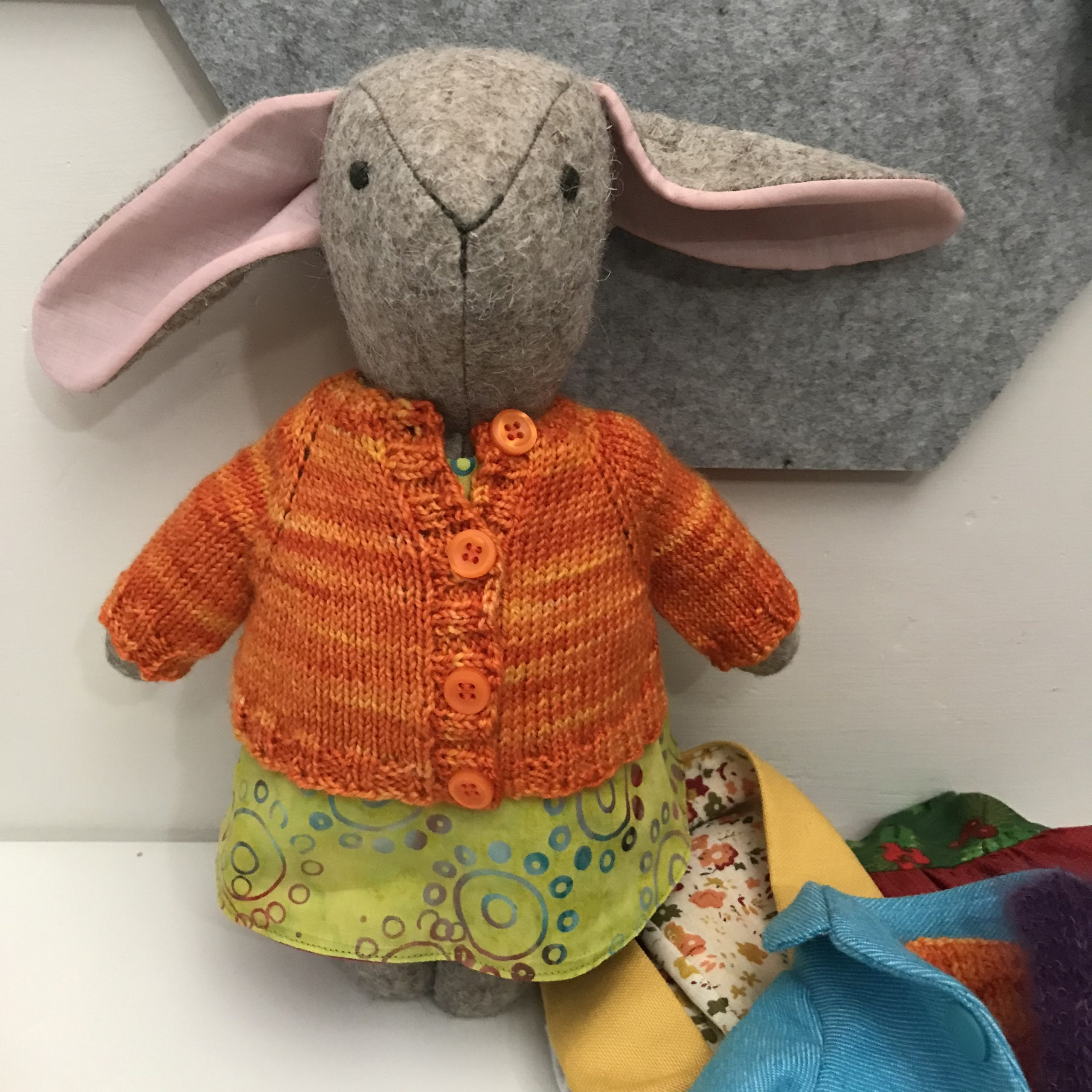 Bunny toy in a wee orange sweater.